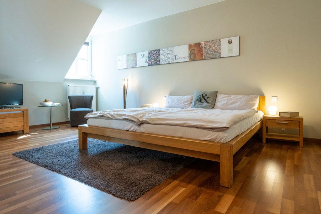 Doppelbett in einem Zimmer des Wein- & Tafelhaus