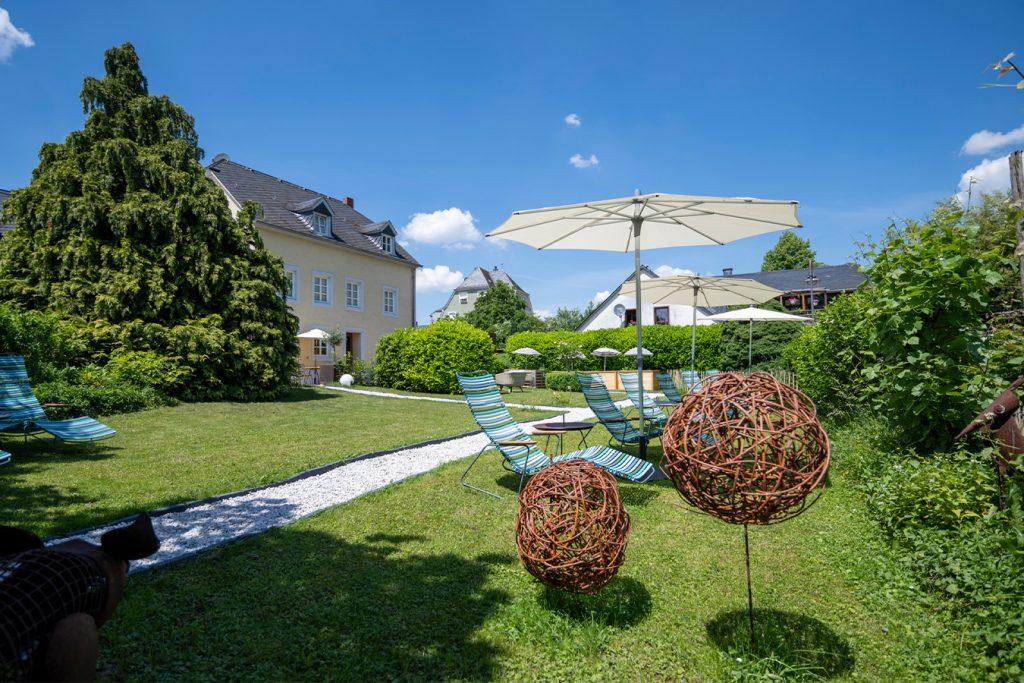 Außenbereich des Wein- & Tafelhaus. Zu sehen sind liegen und Sonnenschirme